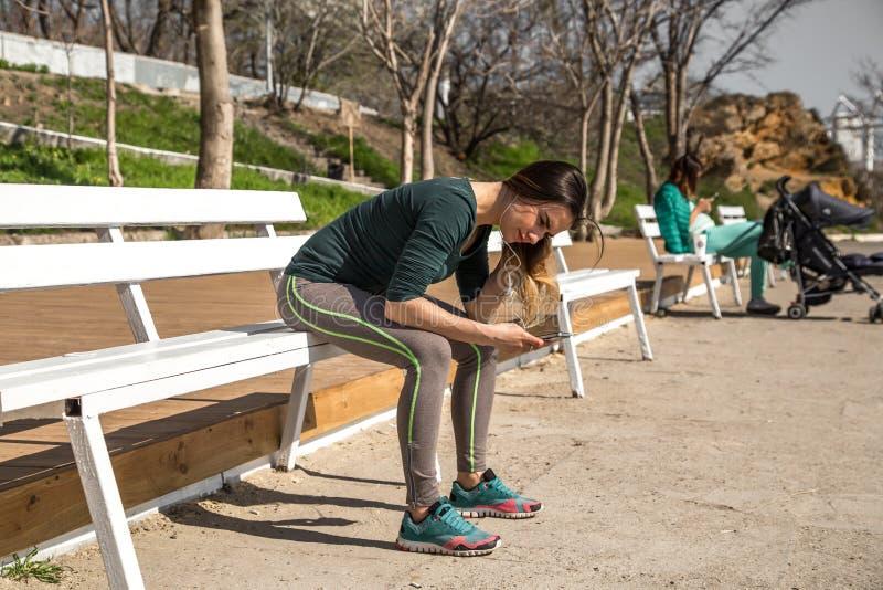 Dziewczyna słucha muzyka w sportswear na ławce fotografia royalty free