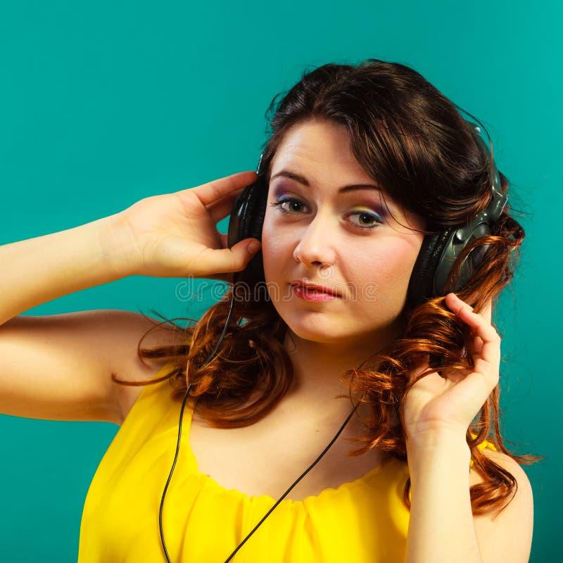 Dziewczyna s?ucha muzyki mp3 relaksowa? w du?ych he?mofonach obrazy stock