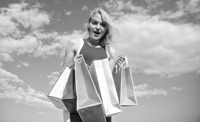 Dziewczyna satysfakcjonująca z zakupami Kobiety czerwieni suknia niesie wiązek torba na zakupy niebieskiego nieba tło Robić zakup obraz royalty free