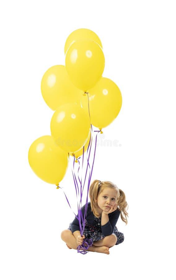 Dziewczyna siedząca i z kolorowymi balonami zdjęcia royalty free