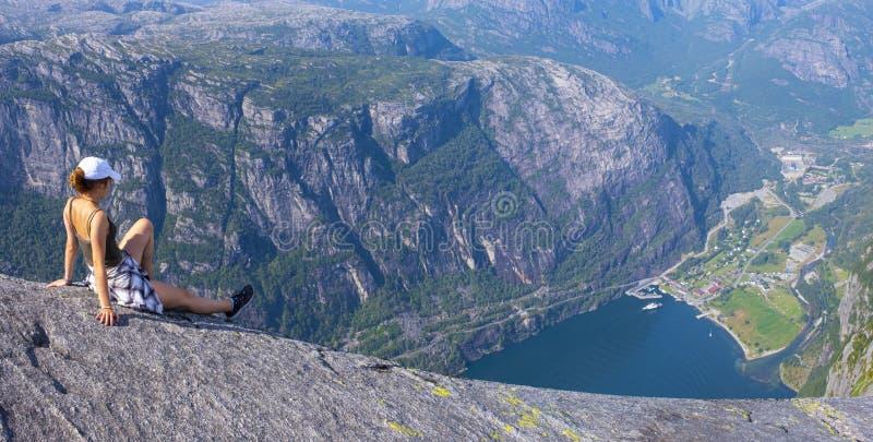 Dziewczyna siedzÄ…ca podziwiajÄ…ca krajobraz nad Lysefjord zdjęcia stock