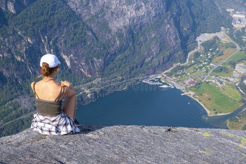 Dziewczyna siedzÄ…ca podziwiajÄ…ca krajobraz nad Lysefjord zdjęcia royalty free