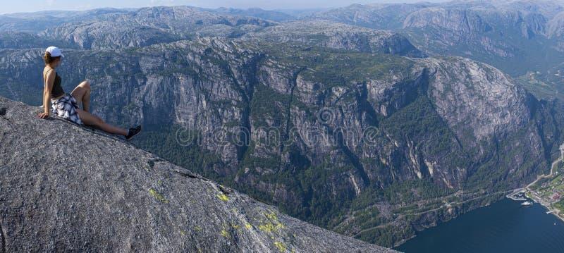 Dziewczyna siedzÄ…ca podziwiajÄ…ca krajobraz nad Lysefjord fotografia stock