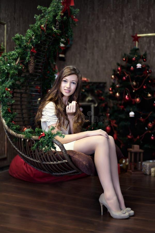 Dziewczyna siedzi bezczynnie relaksuje w holu podczas świętowania boże narodzenia i nowy rok z choinką zdjęcie stock