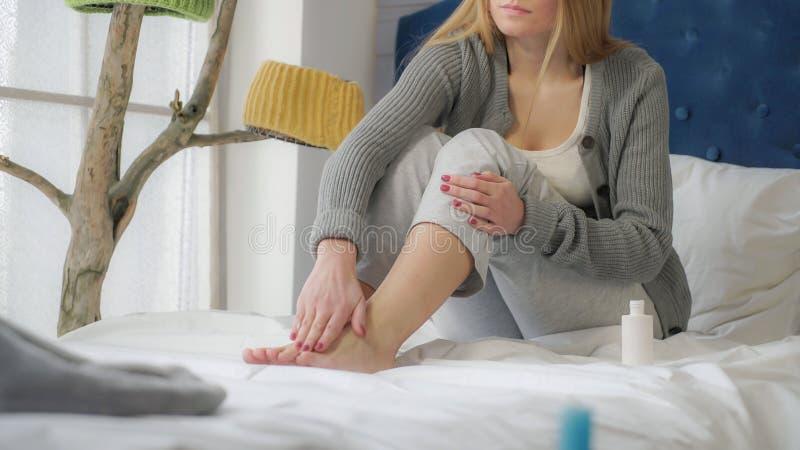 Dziewczyna siedzi na łóżkowych pocieraniach kremowych w jego nogę obraz stock