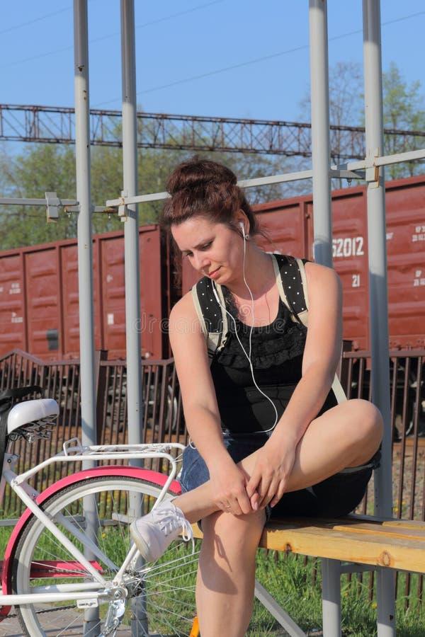 Dziewczyna siedzi na ławce i słucha muzyka W pobli?u jest jej rower zdjęcie royalty free