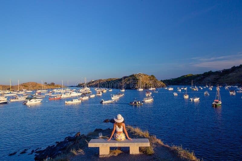 Dziewczyna siedzi na ławce przed piękną zatoką z jachtami zdjęcia royalty free