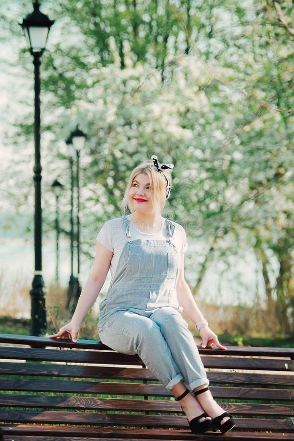Dziewczyna siedzi na ławce z sprig wewnątrz czereśniowi okwitnięcia zdjęcia royalty free