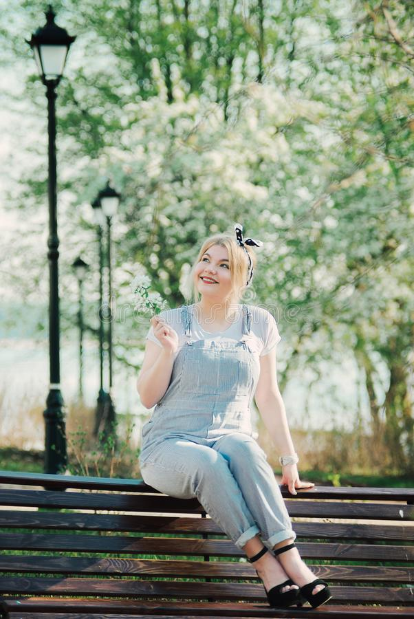 Dziewczyna siedzi na ławce z sprig wewnątrz czereśniowi okwitnięcia zdjęcie royalty free