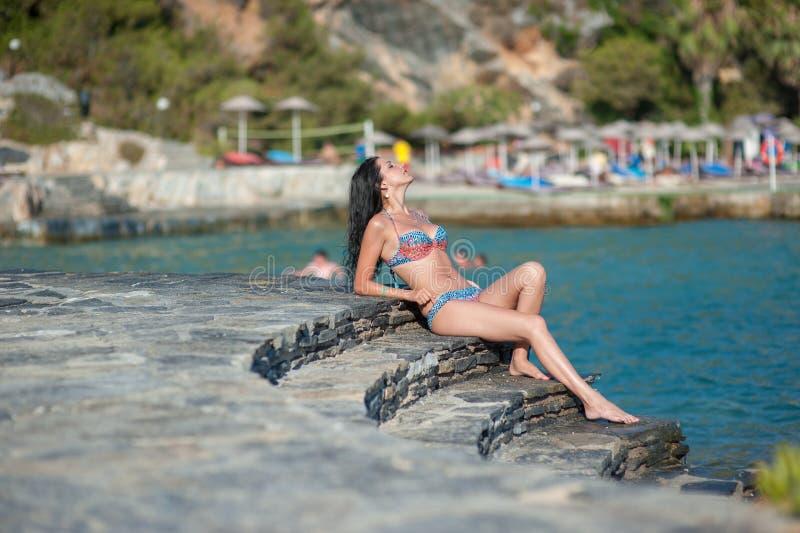 Dziewczyna siedzi na kamiennych krokach morzem Piękna brunetka morzem odpoczynek zdjęcie stock