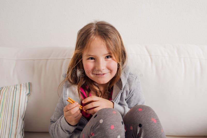 Dziewczyna siedzi na kanapie w domu, je breadsticks zdjęcie royalty free