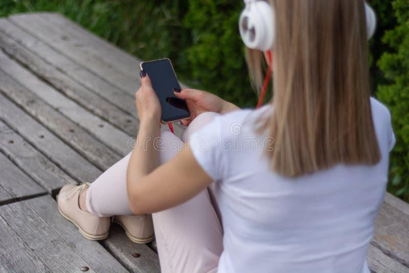 Dziewczyna siedzi na muzyka z smartphone na nogach, he?mofonach i fotografia stock