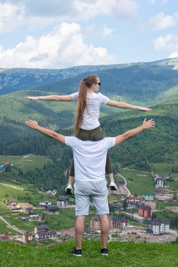 Dziewczyna siedzi na ramionach facet i podziwia góry zdjęcia stock