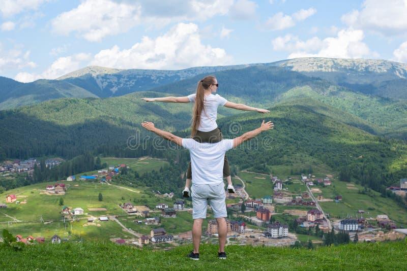 Dziewczyna siedzi na ramionach facet i podziwia góry obraz royalty free