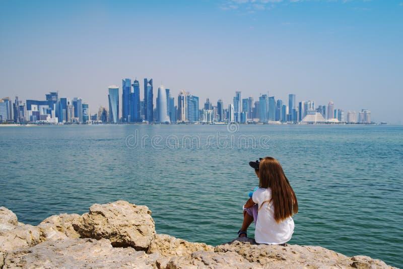 Dziewczyna siedzi na spojrzeniach przy budynkami miasto Katar i oceanie fotografia royalty free
