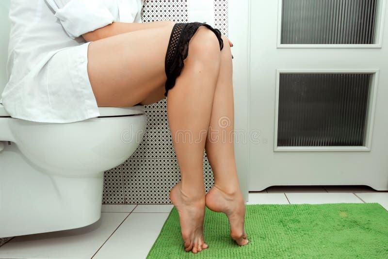 Dziewczyna siedzi na toalecie, cropped wizerunek Pojęcie problemy z krzesłem, jelita, osobista higiena, zdjęcie stock