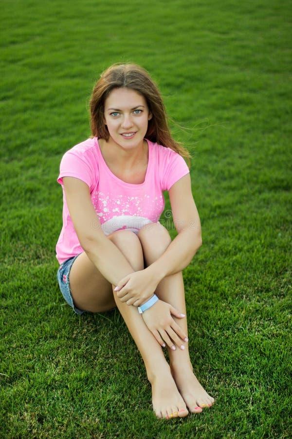 Dziewczyna siedzi na trawie obraz stock
