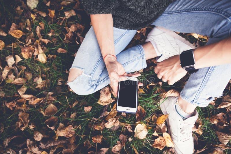 Dziewczyna siedzi na trawie i na spadać jesień liściach z smartp fotografia stock