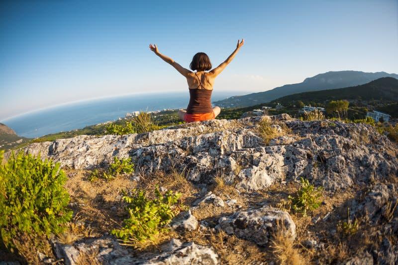 Dziewczyna siedzi na wierzchołku góra przy zmierzchem fotografia stock