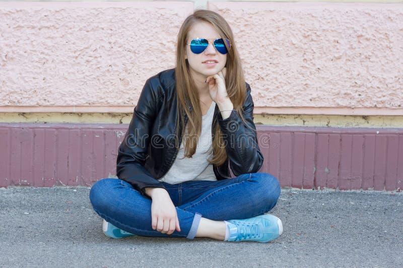 Dziewczyna siedzi na ziemi w cajgach zdjęcie royalty free