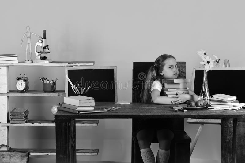 Dziewczyna siedzi przy drewnianym biurkiem z kolorowym materiały, kwiatami i owoc, Uczennica z gderliwą twarzą trzyma książki ste zdjęcia royalty free