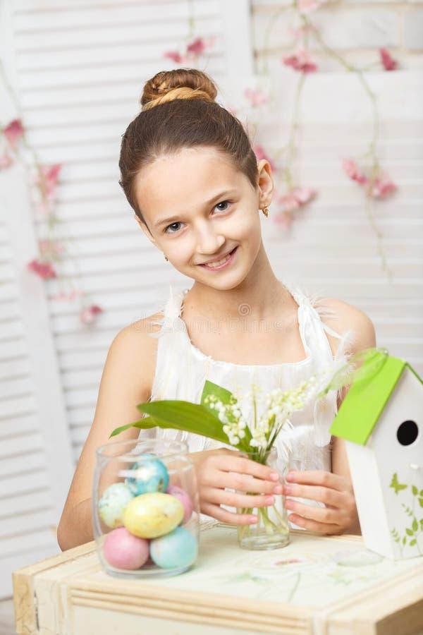 Dziewczyna siedzi przy stołem, trzymający kwiaty i malujących jajka fotografia royalty free