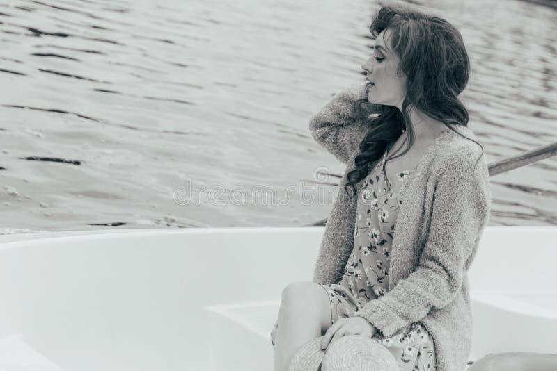 dziewczyna siedzi w białej łodzi na rzece w rękach trzyma kapelusz od słońca Pekin, china zdjęcie stock