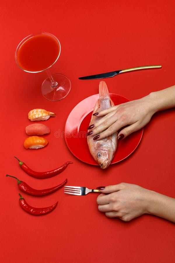 Dziewczyna sieka surowej ryby na czerwonym talerzu na czerwonym stole pojęcie kreatywnie obrazy royalty free