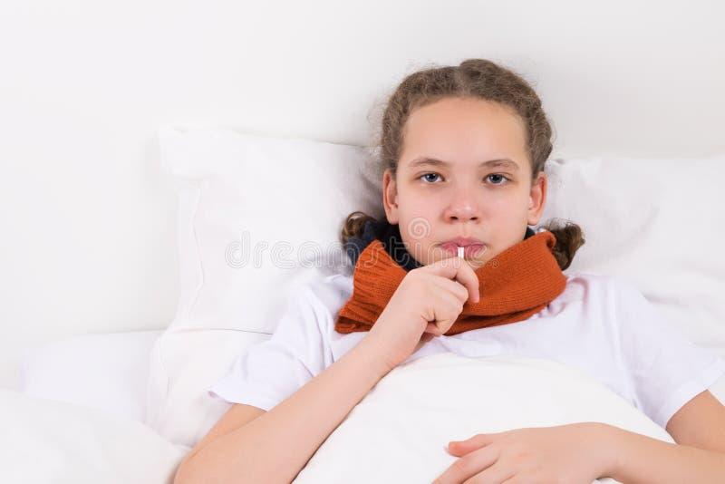 Dziewczyna spadał chorą, kłamstwa na łóżku, miary temperatura fotografia stock
