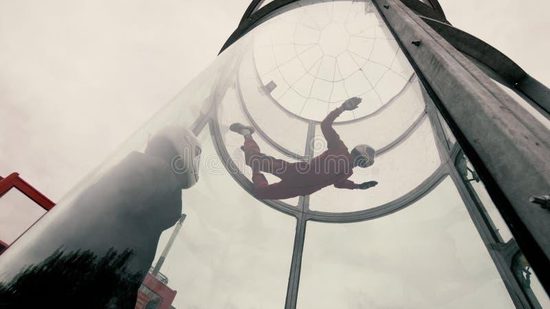 Dziewczyna spadochroniarz wykonuje spadochronowego doskakiwanie w wiatrowym tunelu obrazy royalty free