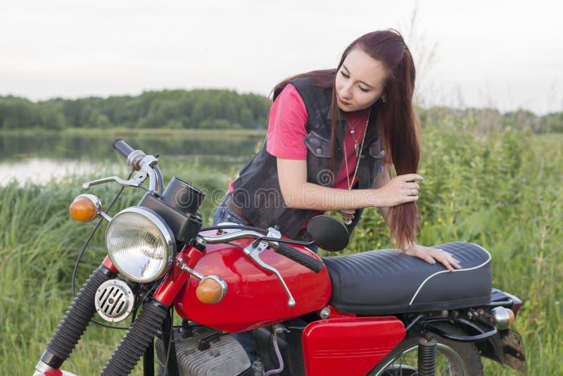 Dziewczyna stoi blisko roczników spojrzeń w lustrze i motocyklu outdoors obrazy stock