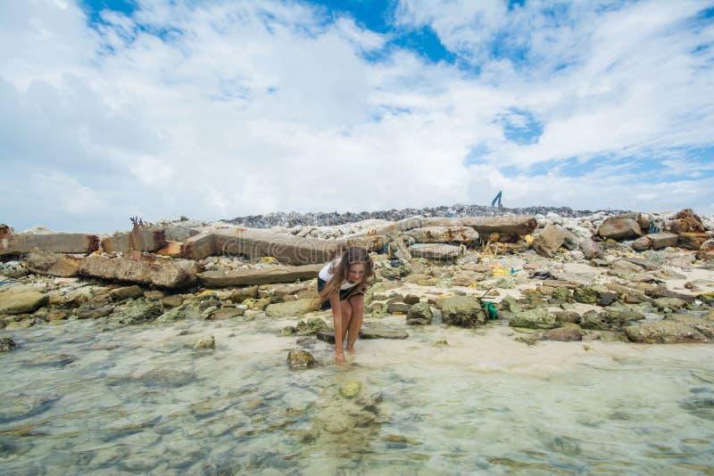 Dziewczyna stoi patrzeć dla skorup w oceanie z śmieciarskim usypem przy tłem fotografia royalty free