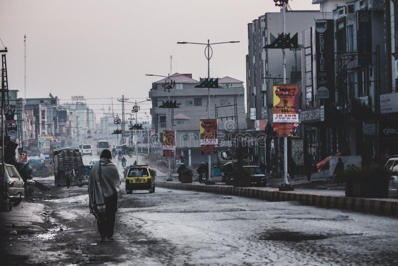 Dziewczyna stoi samotnie w ruchliwie, dotknięty biedą ulicach Islamabad, obrazy royalty free