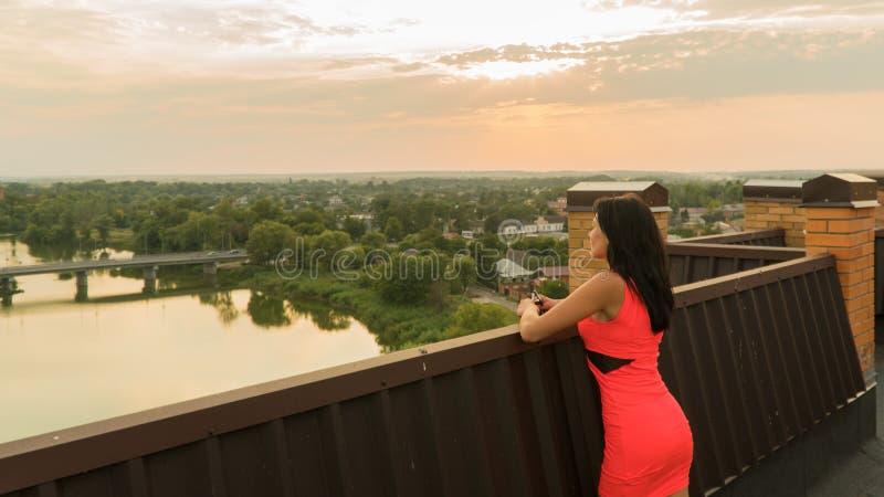 Dziewczyna stojaki na dachu dom sunset wiatr pozyskiwania burzy obrazy stock