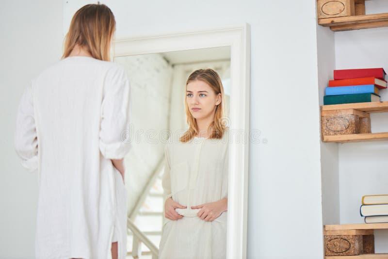 Dziewczyna stojaki przy lustrem i są za żołądkiem obraz royalty free