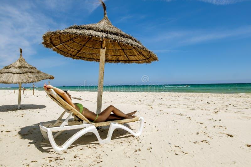 Dziewczyna sunbathing na deckchair pod parasolem o w bikini obraz royalty free