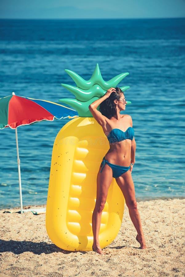 Dziewczyna sunbathing na plaży z lotniczą materac dziewczyna w swimsuit na pogodnej plaży zdjęcia stock