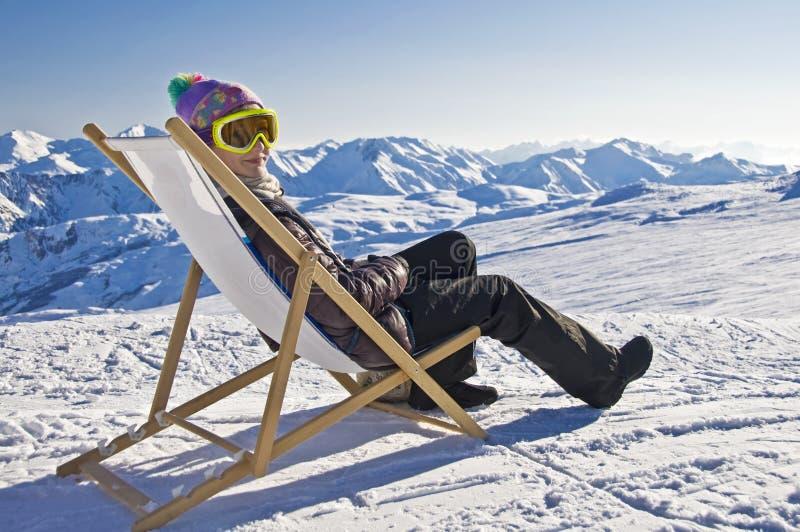 Dziewczyna sunbathing w deckchair na stronie narciarski skłon obrazy royalty free