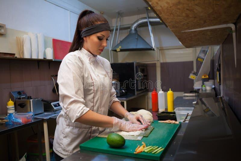 Dziewczyna suszi szef kuchni przygotowywa jedzenie w kuchni przy restauracją fotografia stock