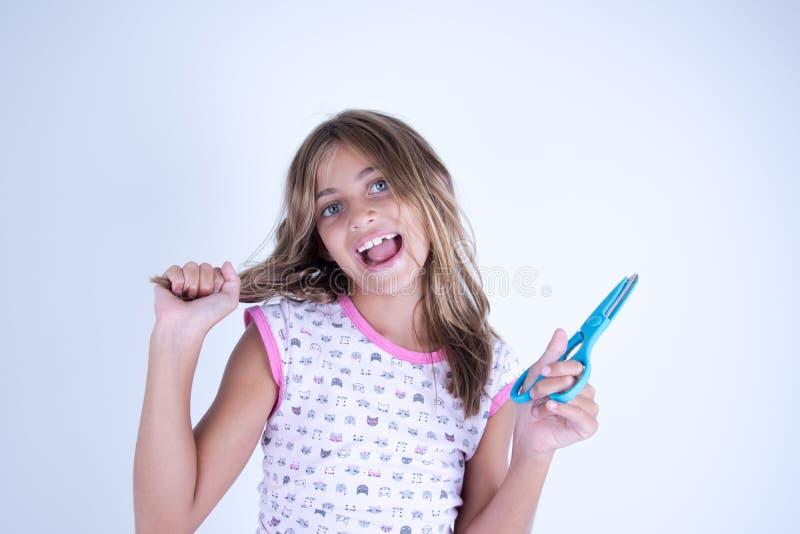 Dziewczyna szczęśliwa z nożycami przygotowywającymi ciąć włosy fotografia royalty free