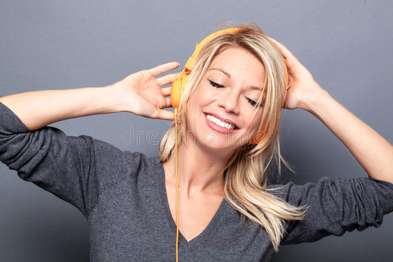 Dziewczyna taniec w słuchaniu muzyka na hełmofonach relaksować zdjęcia royalty free