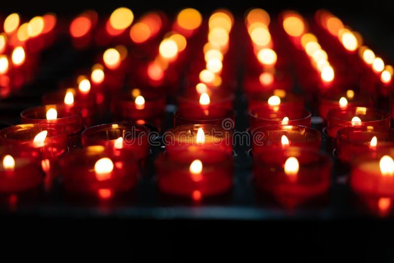 Dziewczyna trzyma świeczkę i ono modli się blisko ołtarza w kościół zdjęcia stock