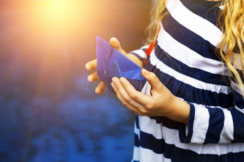 Dziewczyna trzyma błękitnego papieru łódź ja fotografia royalty free