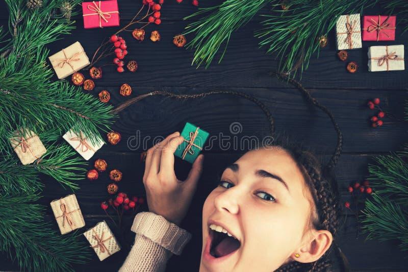 Dziewczyna trzyma Bożenarodzeniowych ono uśmiecha się i prezent zdjęcia royalty free