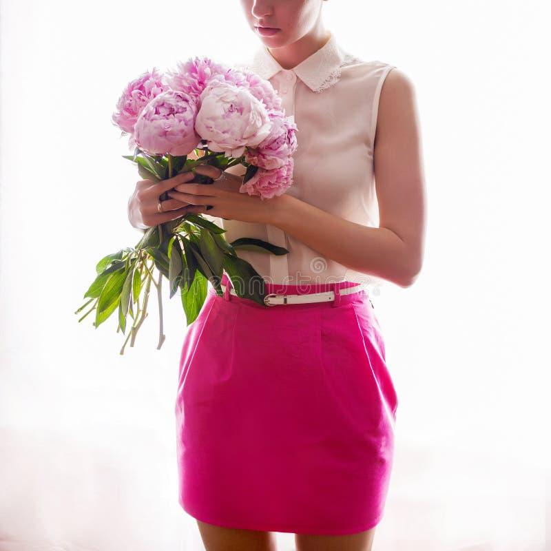 Dziewczyna trzyma bukiet z peoniami w menchii spódnicowej i białej kurtce w rękach obrazy stock