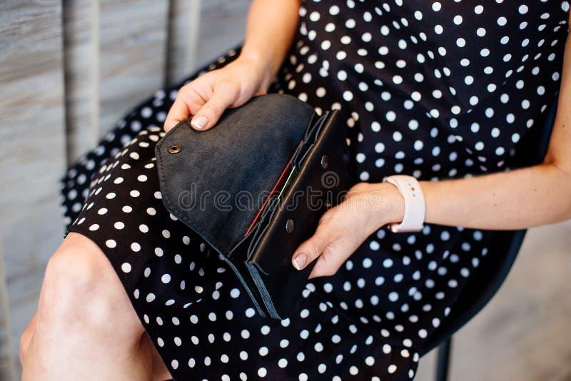 Dziewczyna trzyma czarnego pieniądze portfel obraz stock