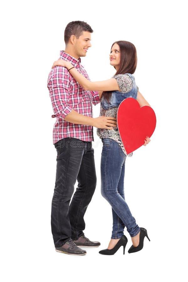 Dziewczyna trzyma czerwonego serce i jej chłopaka obrazy stock