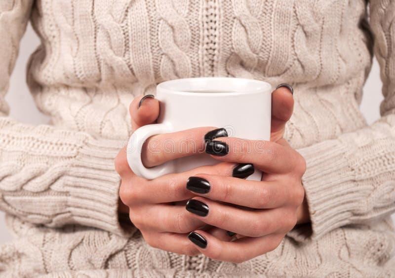 Dziewczyna trzyma filiżankę herbata w jej rękach z czerń gwoździami w pulowerze, zamyka up zdjęcia royalty free