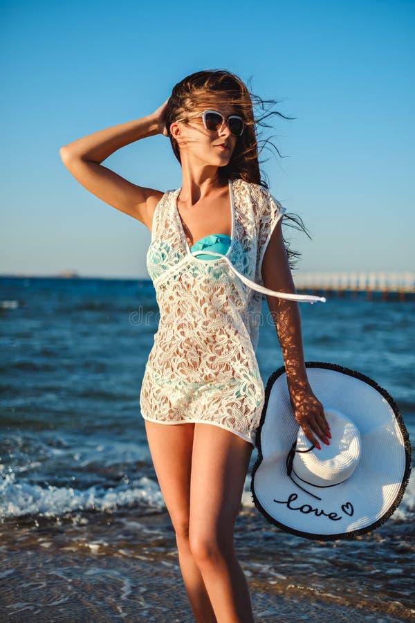 Dziewczyna trzyma jej kapelusz na plaży w wietrznym dniu fotografia royalty free