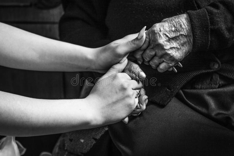 Dziewczyna trzyma jej starej babci dla jej ręki w czarny i biały obrazy stock